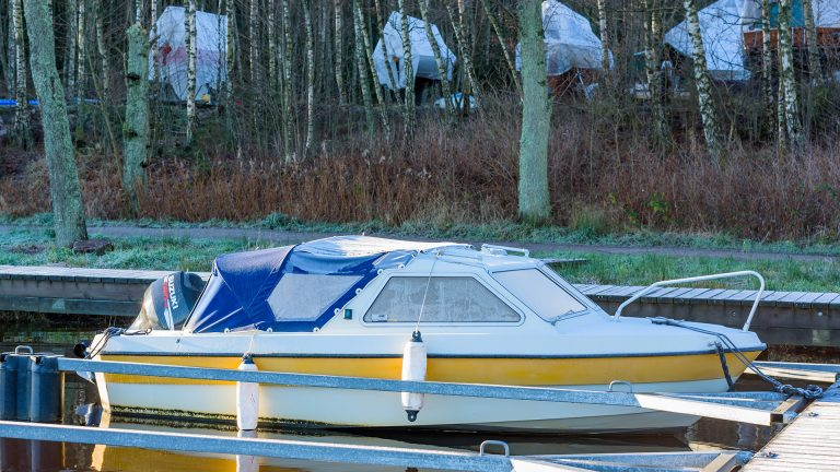 Nattraby: Documentary of everyday life and environment. Motorboat in marina with frost on windows and tarp. Other boats in winter storage on land in background.