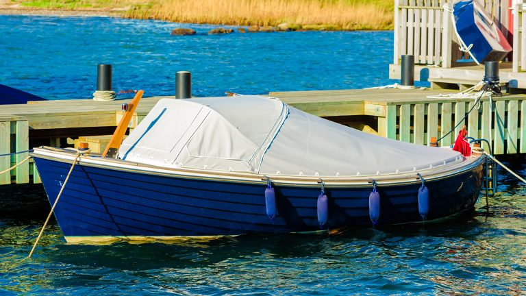 Blue motorboat covered with tarp, moored by a wooden pier.