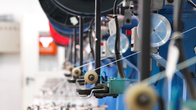 """""""detail of an indoor industrial production line, in a thread factory"""""""