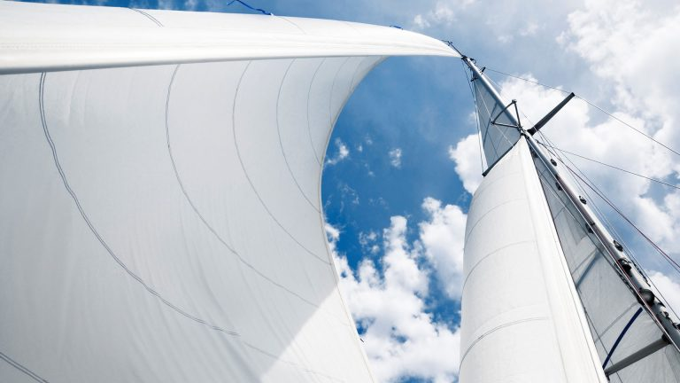 Three sails of the yacht billowing in the wind.