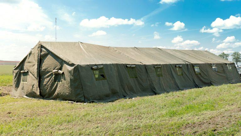 Big military tent in the field agaist bright blue sky